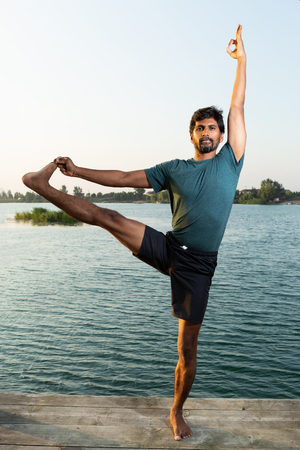 Indian man practicing yoga pose near water standing on wooden path with natural background