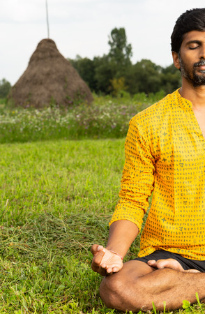 Half-view of relaxed indian man practicing lotus pose in the grass with natural background Stock Photo