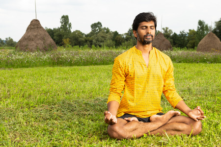 Indian man with closed eyes relaxing by yoga in lotus position with hands on knees in natural background