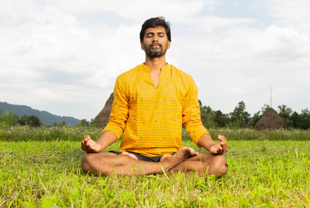 Indian man yogi in lotus pose resting hands on knees sitting in grass as natural background