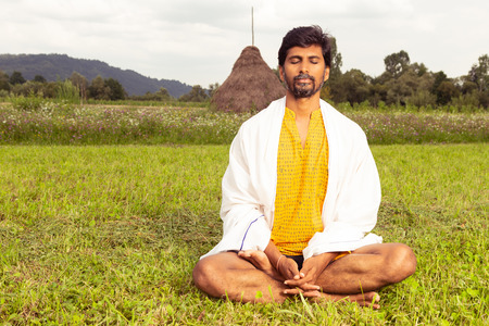 Indian yoga master practicing meditation in lotus postion joined hands with white blanket on expressing calm and relaxation in natural grass background Reklamní fotografie