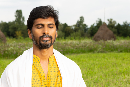 Indian male person or yogi close-up of calm expression with eyes closed wearing white over yellow shirt with natural background