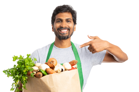 Smiling grocery store or supermarket employee presenting fresh products in paper bag with index finger isolated on white