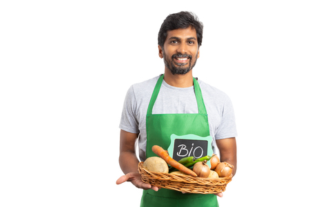 Indian hypermarket or supermarket employee with happy exptession holding grocery basket with bio text on sign isoalted on white 免版税图像