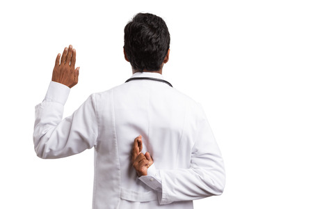 Fake oath made by indian doctor with fingers crossed behind back and raised palm isolated on white background Archivio Fotografico