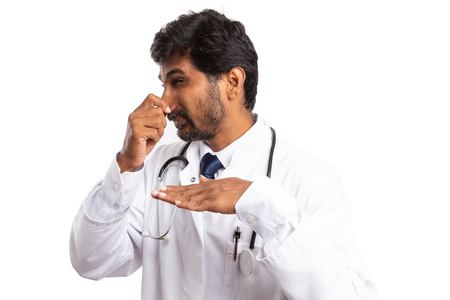 Indian doctor man holding nose with hand and expressing disgust as bad smell concept isolated on white background Imagens