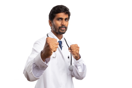 Angry indin male doctor showing fists with irritated expression as ready to fight concept isolated on white