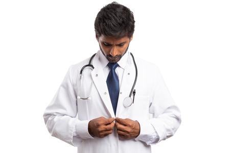 Male indian medic buttoningwhite medical coat while looking isolated on studio background