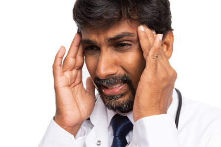 Indian tired doctor with suffering expression having headache and using fingers to touch temples close-up isolated on white 免版税图像