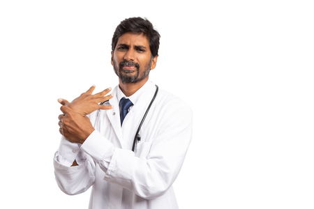 Indian doctor man holding sprained painful wrist with hand isolated on white studio background