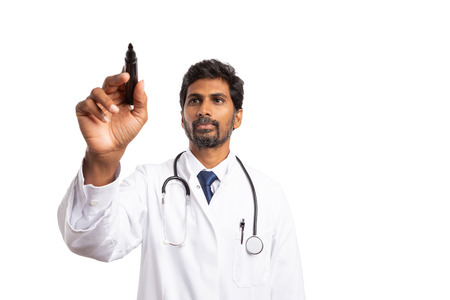 Indian doctor writing with marker on transparent screen as copyspace for advertising isolated on white
