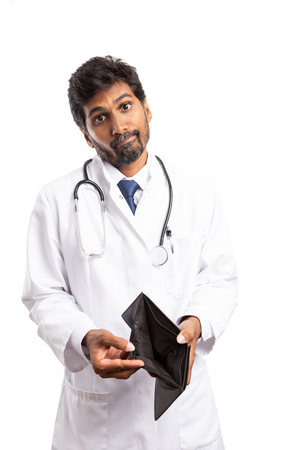 Doctor or medic  man showing empty wallet with apologetic expression isolated on white studio background Foto de archivo