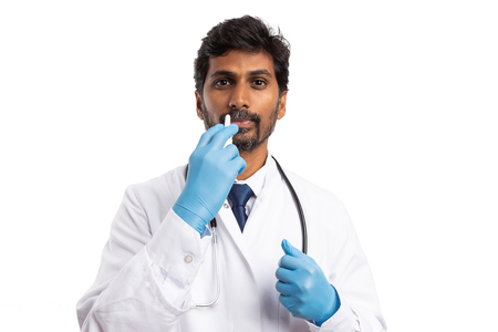 Indian doctor man using nasal spray as flu or allergy concept isolated on white studio background