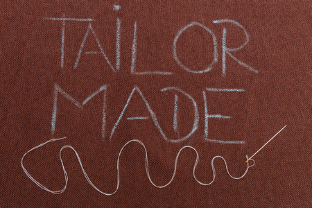 Tailor made blue text on brown fabric background underlined with winding thread in needle