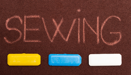 Sewing text underlined by yellow, blue and white tailoring chalks on brown fabric as background Фото со стока