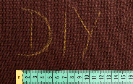 DIY text meaning do it yourself on brown fabric underlined with green measuring tape for tailoring