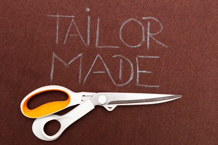 Scissors underlining tailor made text on brown fabric as background