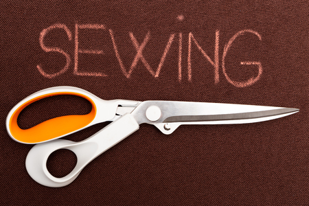 Sewing text on brown material background underlined with pair of scissors
