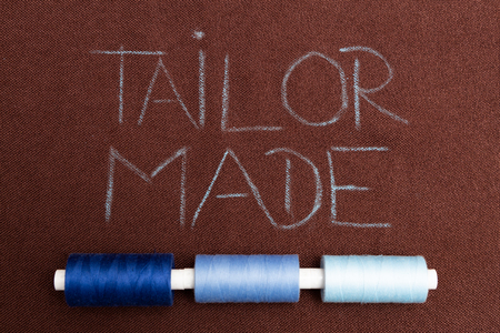 Tailor made written on brown fabric as background underlined with blue thread spools
