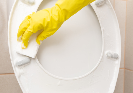 Toilet seat being cleaned with white sponge by person wearing sanitary gloves close-up Stock fotó