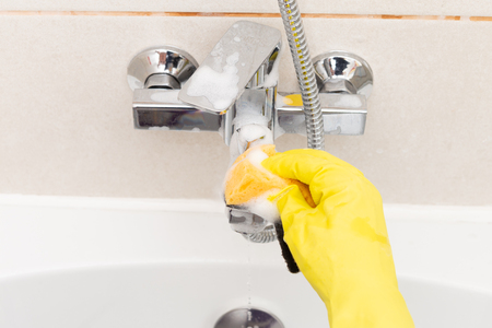 Person disinfecting inox water tap while wearing yellow rubber sanitary gloves