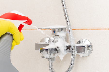 Person spraying metallic water tap from shower wearing sanitary rubber gloves as bathroom cleaning concept