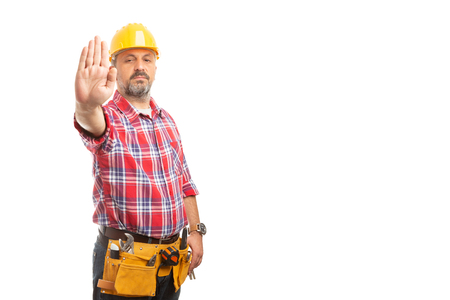Builder showing palm as do not cross gesture with serious expression isolated on white studio background
