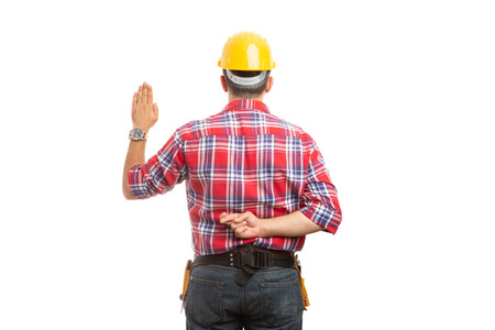Lying constructor doing unsincere oath with palm raised and crossed fingers behind back isolated on white background