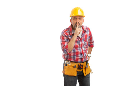 Constructor making shush gesture with index finger as secret concept isolated on white studio background