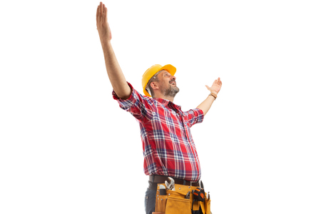 Cheerful constructor holding hands up as celebrating success sign isolated on white studio background