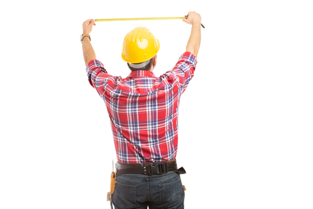 Builder measuring blank copyspace behind with back to camera isolated on white studio background Stock Photo
