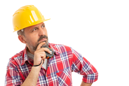 Close-up of male constructor touching chin with hand holding measuring tape as thinking isolated on white background