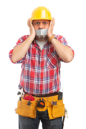Scared male constructor with grey duct tape on mouth as silence concept isolated on white studio background