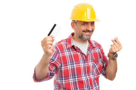 Smiling builder showing card and making money gesture with fingers isolated on white studio background Stock Photo