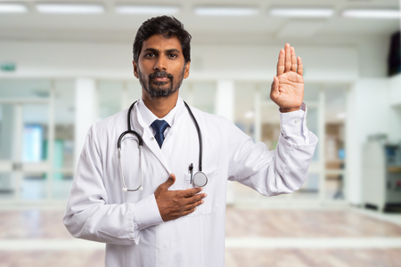 Indian male medic or doctor swearing with hand on heart and palm raised as solemn hippocratic oath concept in hospital hallway background Stock Photo