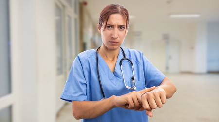 Angry nurse woman pointing at wrist with index finger as late for work concept Stock fotó
