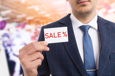 Salesman wearing suit and tie advertising sale by using white card with text and per-cent symbol