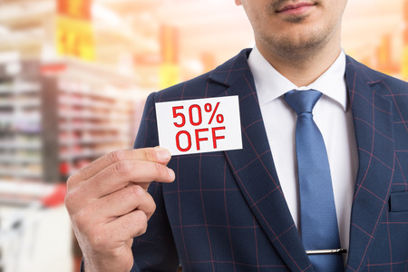 Man presenting white card with fifty per-cent off concept as advertising discount