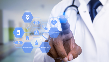 Close-up of indian physician choosing with index finger medical text hexagon button on transparent display as futurist technology medicine concept Archivio Fotografico