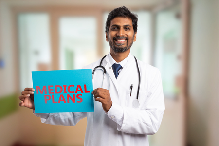 Smiling indian doctor man holding in hand blue paper sign with medical plans red text as planning concept