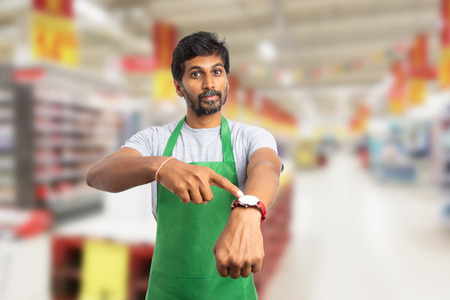 Upset indian male supermarket employee or manager with serious expression pointing with index finger at watch on wrist as you are late for work concept Banque d'images - 118780887