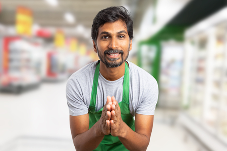 Indian worker man at supermarket or hypermarket with joint hands as begging gesture wearing green apron