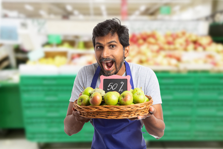 Indian man working at hypermarket or supermarket advertising fifty percent sale at apples with friendly excited expression and holding basket