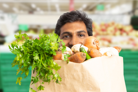 Close-up of indian male supermarket or hypermarket employee hiding behind grocery paper bag