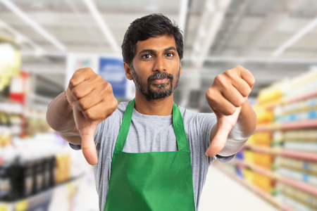 Indian supermarket or hypermarket employee man making double thumbs-down gesture as dislike concept