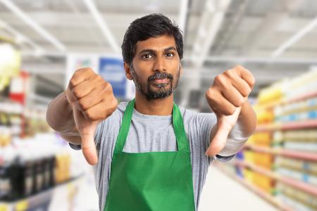 Indischer Supermarkt- oder Hypermarktangestellter, der doppelte Daumen-nach-unten-Geste als Abneigungskonzept macht Standard-Bild