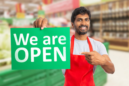Friendly man working at hypermarket or supermarket pointing with index finger at we are open text on green paper