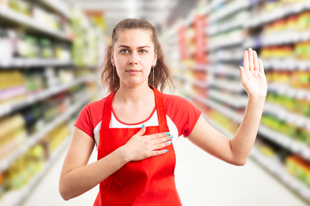 Female hypermarket or supermarket employee making honest oath with hand on heart and palm up Banco de Imagens