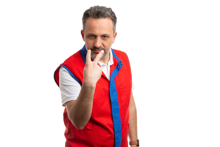 Angry supermarket or hypermarket employee supervisor pointing at eyes as looking at you gesture isolated on white background Stock Photo