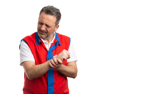 Male supermarket or hypermarket employee touching sprained wrist with painful expression isolated on white studio background